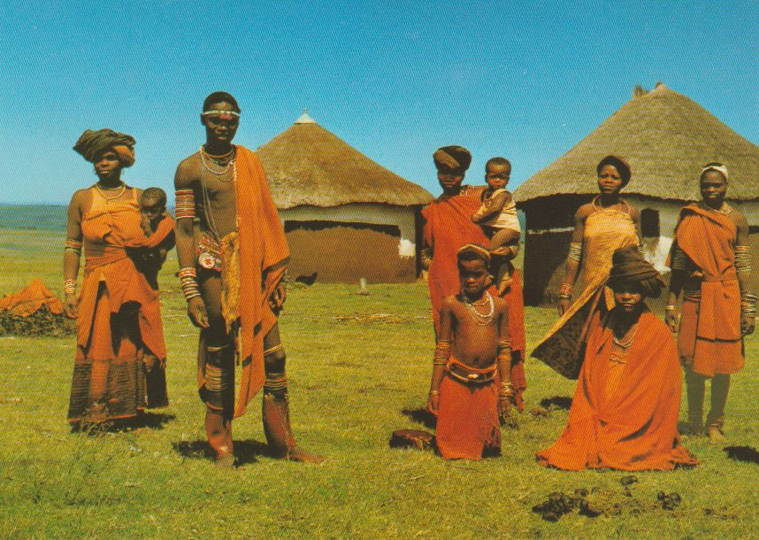 "Transkei Southern Africa Family group wearing the traditional ""red blankes"" of the Xhosas, seen against a typical countryside of thatched homesteads and open grasslands. Postcard 1984"